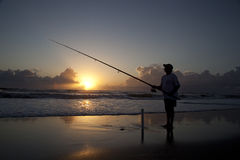 Surf fishing. Fisherman seen in silhouette surf fishing at sunrise on the East Coast of Florida Stock Photo