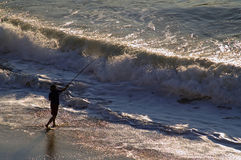 Surf Fishing. A Silhouetted man casting his bait into the ocean waves royalty free stock photography