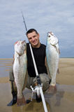 Surf fishing, fish. Surf fisherman holding  two big meager fish Stock Image