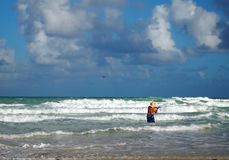 Surf Fishing. A man in a straw hat casts his fishing line out into the surf while standing in the breakers on the beach Royalty Free Stock Photo