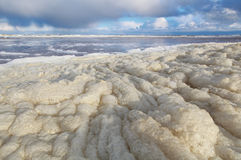 Surf foam on beach after storm Royalty Free Stock Photo