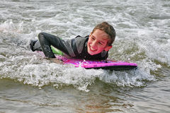 Surf Fun. Young girl boogie boarding in surf in cornwall, england Royalty Free Stock Photos