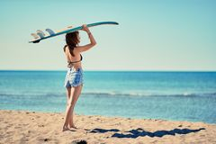 Surf girl go to surfing- Beautiful girl surfer looking for the w. Surf girl go to surfing- Beautiful smiling girl surfer looking for the waves royalty free stock photo