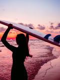 Surf girl with long hair go to surfing. Silhouette of a woman with surfboard on a beach at sunset or sunrise. Surfer and ocean Stock Image