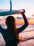 Surf girl with long hair holding surfboard on beach at sunset or sunrise. Surfer and ocean Royalty Free Stock Photo