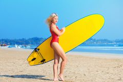 Surf girl in red swimsuit holding a surfboard and is going to go surfing royalty free stock image