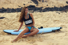 Surf girl with surfboard on beach. Sports. Surfing. Healthy Active Lifestyle. Summer Vacations. Surf girl in bikini sitting on surfboard and sunbathing at sandy Stock Images