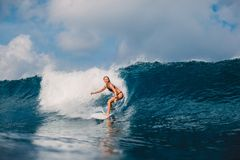 Surf girl at surfboard on barrel wave. Woman and surfing Stock Image
