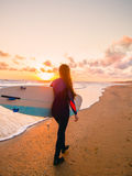 Surf girl with surfboard at sunset and ocean in Canada Royalty Free Stock Photo