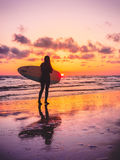 Surf girl with surfboard with warm sunset or sunrise colors Stock Photography