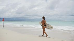 Surf Girl Walking Surfboard Beach Tropical Slowmotion. Slowmotion footage of a surf girl walking at a beautiful beach on Bali, Indonesia stock video footage
