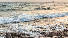 Surf on Gulf of Aqaba beach on Red Sea in winter. Travel to Middle East country Kingdom of Jordan - surf on beach of Gulf of Aqaba on Red Sea in winter evening Stock Photo
