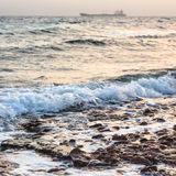 Surf on Gulf of Aqaba coast on Red Sea in winter. Travel to Middle East country Kingdom of Jordan - surf on coast of Gulf of Aqaba on Red Sea in winter evening Stock Photo