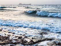 Surf on Gulf of Aqaba shore on Red Sea in winter. Travel to Middle East country Kingdom of Jordan - surf on shore of Gulf of Aqaba on Red Sea in winter evening Stock Photography