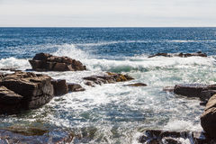 Surf Hitting Rocks in Blue Water Royalty Free Stock Photography