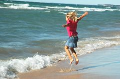 Surf Jumper Girl. Carefree young girl jumping in the surf Royalty Free Stock Image