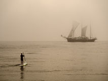 Surf kayaker and a sailing ship Stock Photo