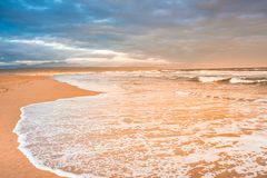 The surf of a large white wave fills the foreground, as it breaks on Plettenberg Bay Beach at sunset. Garden Route, Western Cape, South Africa stock image