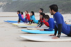 Surf lessons in portugal. Surf class first lesson practicing on the sand the take off Royalty Free Stock Photography