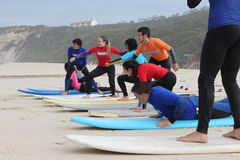 Surf lessons in portugal. Surf class first lesson practicing on the sand the take off Royalty Free Stock Photos