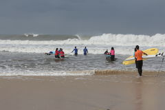 Surf lessons in portugal. Surf coach teaching a surf class that going to water for the first time Stock Photography