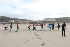 Surf lessons in portugal. Surf coach teaching a surf class practice the take off on the sand Royalty Free Stock Image