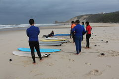 Surf lessons in portugal. Teachear explain how to take off on a surf board Royalty Free Stock Photography