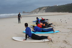 Surf lessons in portugal. Teachear explain to a class how to take off on a surf board Royalty Free Stock Photography