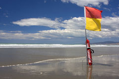 Surf Lifeguard. Surf Lifesaving flag and buoyancy aid on a New Zealand Beach Royalty Free Stock Images