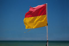 Surf lifesaving flag on beach. Royalty Free Stock Photo