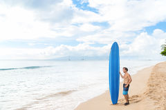 Surf lifestyle young man surfer relaxing on beach. Alone young surfer relaxing looking out to ocean waiting for surfing waves at hawaiian Kaanapali beach in Maui stock images