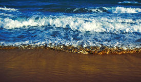 Surf line. Vivid blue waves running to golden sand Royalty Free Stock Photos