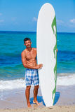 Surf man. Strong young surf man at the beach with a surfboard Stock Photography
