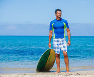 Surf man. Strong young surf man at the beach with a surfboard Royalty Free Stock Photo