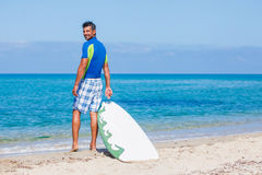 Surf man. Strong young surf man at the beach with a surfboard Stock Image