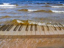 Surf music. Piano keyboard under surf waves Stock Photography