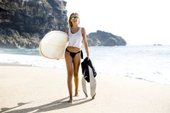 Surf is my passion. Beautiful young surfer girl walking on the beach Stock Photo
