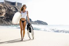 Surf is my passion. Beautiful young surfer girl walking on the beach Stock Photos