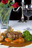 Surf 'n' turf a la carte meal. Beef fillet with shrimps surf 'n' turf a la carte meal with red wine and roses Royalty Free Stock Images