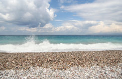 Surf and Pebble Beach. Splashing wave on a pebble beach on the Mediterranean Sea stock images