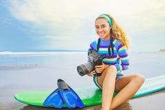 Surf photographer girl. Lovely optimistic surf photographer girl sitting on her board with camera Royalty Free Stock Photography