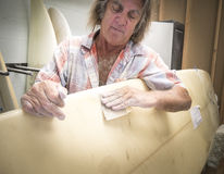 Surf Repair Professional Working On A Surfboard. Surf repair professional craftsman repairing and sanding damaged surfboard in his workshop Royalty Free Stock Photo