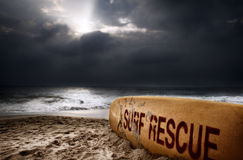 Surf rescue. Surfboard with title surf rescue on the beach near the ocean at dramatic storm sky with dark clouds background Royalty Free Stock Photo