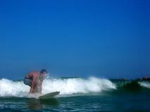 Surf Ride. An action shot of a teenage boy just about to stand up on his surfboard Stock Image