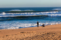 Ocean Waves Beach Surf Riders. Surf riders unidentified sitting on  beach watching the morning waves of size Royalty Free Stock Photo