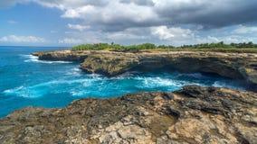 Surf on rocks near island of Lembongan near Bali Royalty Free Stock Photography