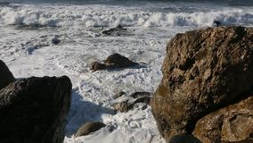 Surf on the rocks in the ocean. Nature stock video footage