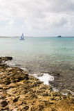 Surf On Rocks with Sailboat Stock Photo