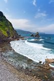Surf at the rocky seashore. Sunny summer day, the blue sky with clouds, rocks with green vegetation Stock Photos