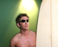 Surf's Up. Male Surfer with surf board in studio royalty free stock photography